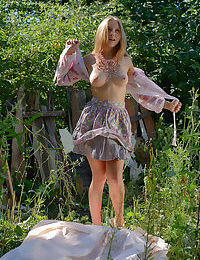 Sweet teen girl with big natural tits poses semi-naked against a fence