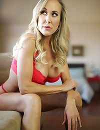 Julia Ann is a MILF stripping down naked on the couch and showing fake tits