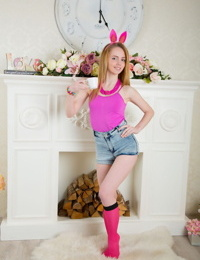 Cute teen girl wears bunny ears while stripping naked by a stack of splits