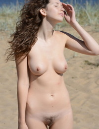 Teen solo girl with nice boobs feels the wind on her bare skin at the beach