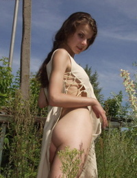 Brunette teen flashes her tight ass in a long dress before parting her pussy