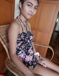 Petite Asian teen Pauw takes off her gown and flaunts her tits and hairy kitty